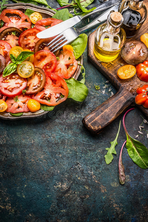 Tomatoes salad with various colorful tomatoes, olives oil and Balsamic vinegar . Plate with tomatoes salad, cutlery and ingredien. Ts on dark rustic background stock image