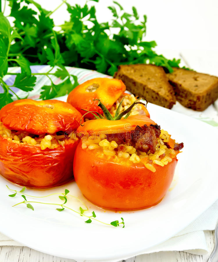Tomatoes stuffed with bulgur in plate on light board royalty free stock image