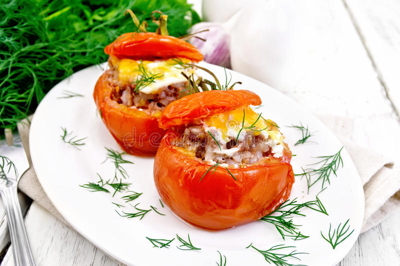 Tomatoes stuffed with meat and rice with dill in plate on board royalty free stock photography