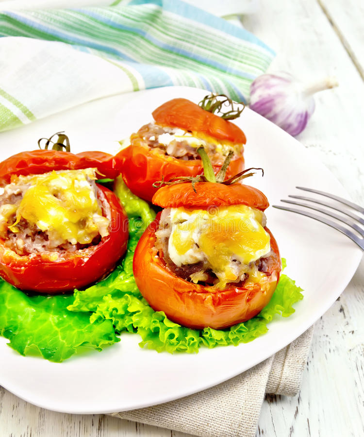 Tomatoes stuffed with rice and meat with lettuce in plate on light board stock images