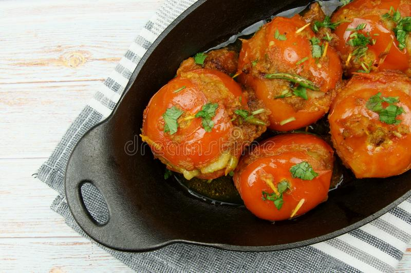 Tomatoes stuffed with a spicy mixture of mashed potatoes in an Indian gravy or curry. Tangy, homemade, summer, cooking, tomatos, gastronomy, culinary, garlic royalty free stock photography