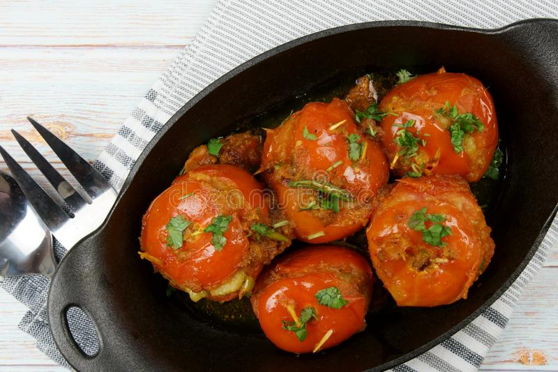 Tomatoes stuffed with a spicy mixture of mashed potatoes in an Indian gravy or curry. Tangy, homemade, summer, cooking, tomatos, gastronomy, culinary, garlic royalty free stock image