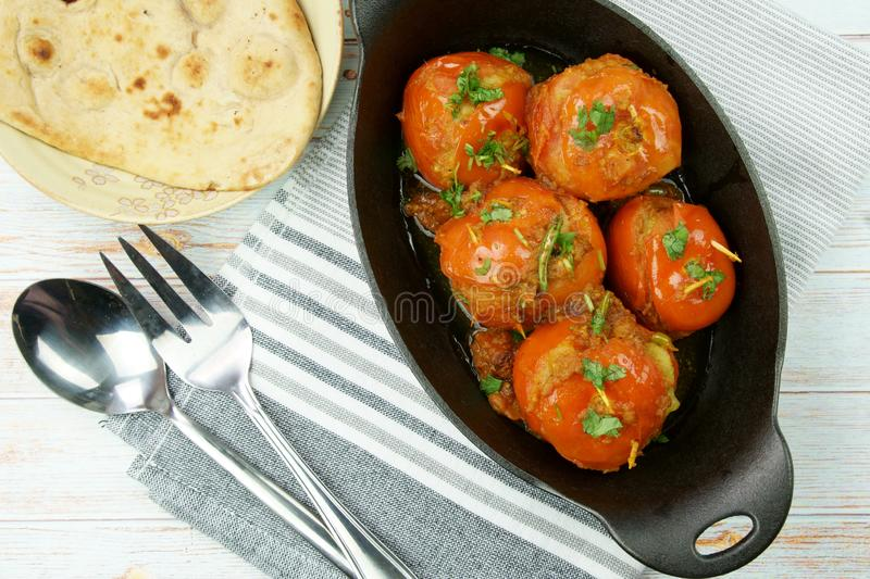 Tomatoes stuffed with a spicy mixture of mashed potatoes in an Indian gravy or curry. Tangy, homemade, summer, cooking, tomatos, gastronomy, culinary, garlic stock photography