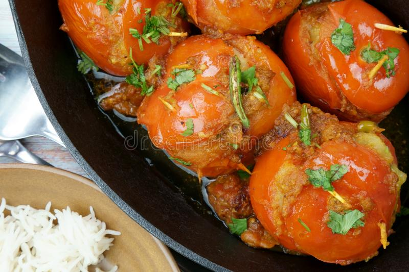Tomatoes stuffed with a spicy mixture of mashed potatoes in an Indian gravy or curry. Tangy, homemade, summer, cooking, tomatos, gastronomy, culinary, garlic stock image