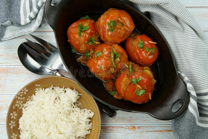 Tomatoes stuffed with a spicy mixture of mashed potatoes in an Indian gravy or curry. Tangy, homemade, summer, cooking, tomatos, gastronomy, culinary, garlic royalty free stock photos