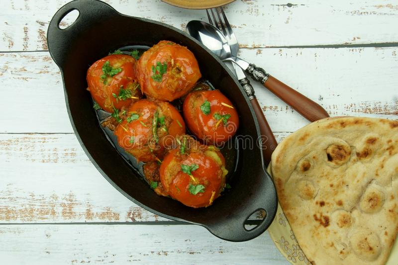 Tomatoes stuffed with a spicy mixture of mashed potatoes in an Indian gravy or curry. Tangy, homemade, summer, cooking, tomatos, gastronomy, culinary, garlic stock photo
