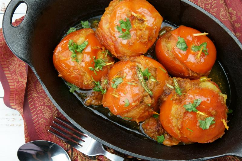 Tomatoes stuffed with a spicy mixture of mashed potatoes in an Indian gravy or curry. Tangy, homemade, summer, cooking, tomatos, gastronomy, culinary, garlic royalty free stock images