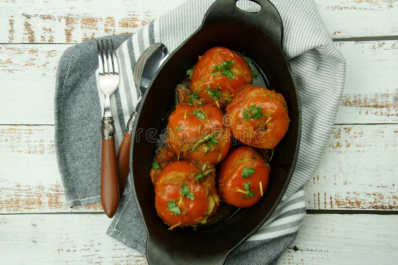 Tomatoes stuffed with a spicy mixture of mashed potatoes in an Indian gravy or curry. Tangy, homemade, summer, cooking, tomatos, gastronomy, culinary, garlic royalty free stock photo