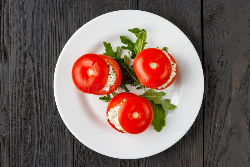Tomatoes stuffed with spinach, cheese and herbs, close up. Delicious and nutritious vegetarian meal royalty free stock image