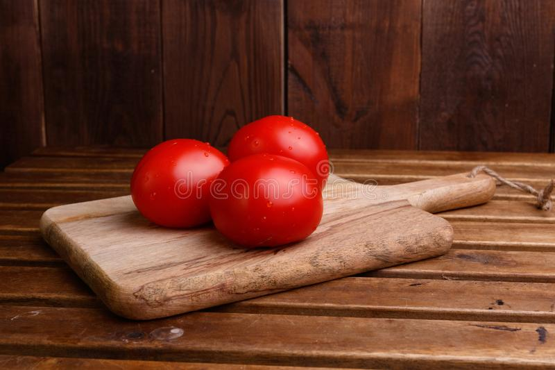 Three whole tomatoes lie on the kitchen wooden board. Close-up stock photos