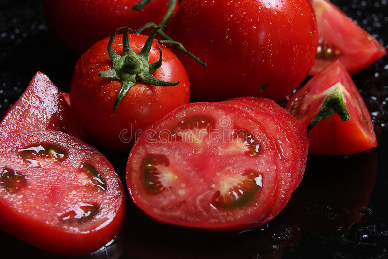 Tomatoes under water drops, red background stock images