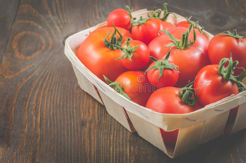 tomatoes in a wattled basket/tomatoes in a wattled box on a dark wooden background, selective focus and copyspace stock photography
