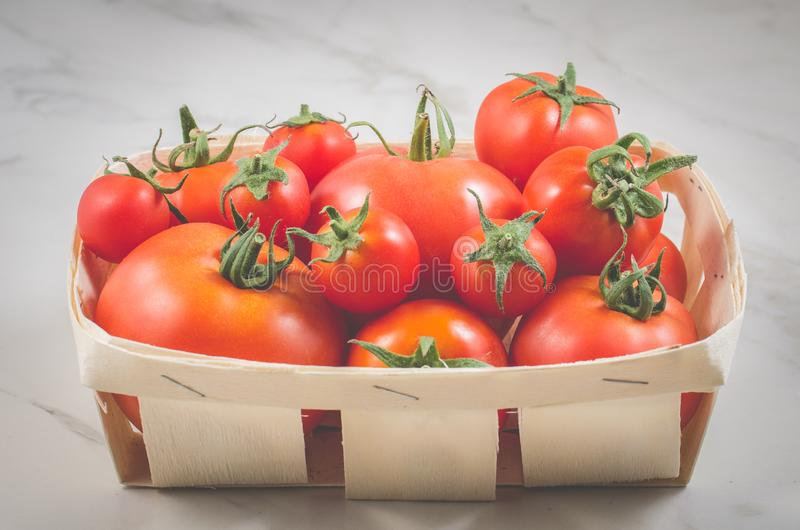 Tomatoes in a wattled basket/tomatoes in a wattled basket on a marble background, selective focus royalty free stock image