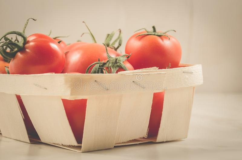 Tomatoes in a wattled box/tomatoes in a wattled box on a white marble background. Basket, red, food, vegetable, ripe, fresh, green, healthy, diet, nature royalty free stock photos