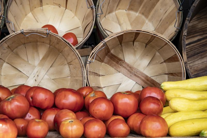 Tomatoes and yellow squash in front of wooden slat baskets at the market.  royalty free stock photography
