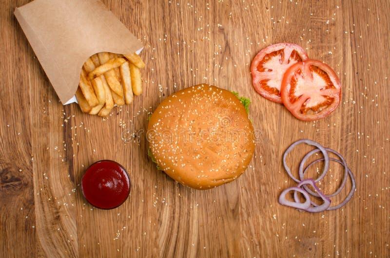 Χάμπουργκερ στον ξύλινο πίνακα με τις τηγανιτές πατάτες Εύγευστο μεσημεριανό γεύμα με το τυρί, τα tomatoos και τη σαλάτα στοκ εικόνες