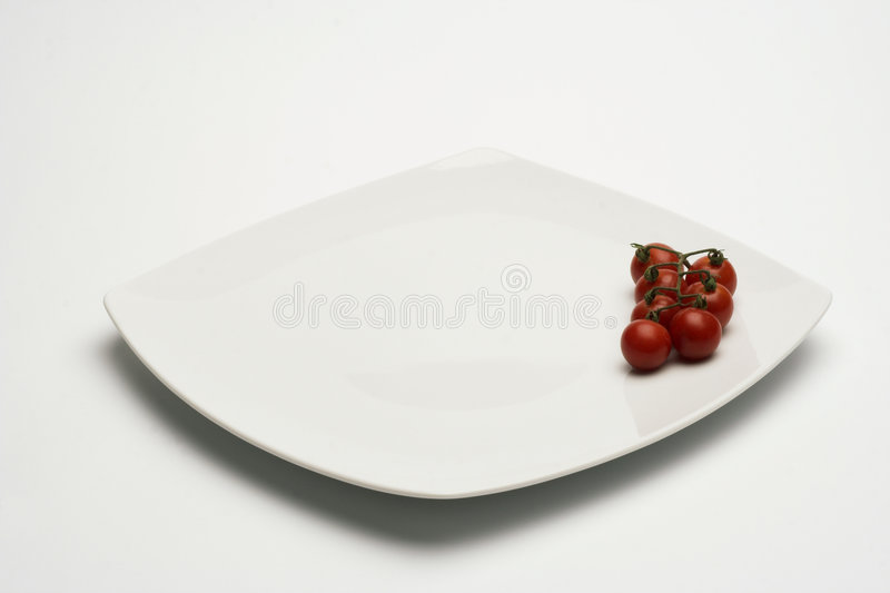 Tomatos in white plate royalty free stock photography
