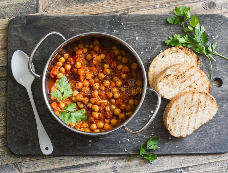 Tomatsås bräserade kikärtar i en kruka och grillade bröd Läcker vegetarisk lunch på en lantlig träbakgrund royaltyfri fotografi