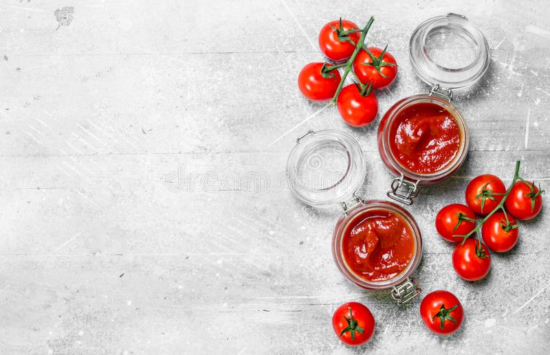 Tomatsås i en krus med körsbärsröda tomater på en filial royaltyfri bild