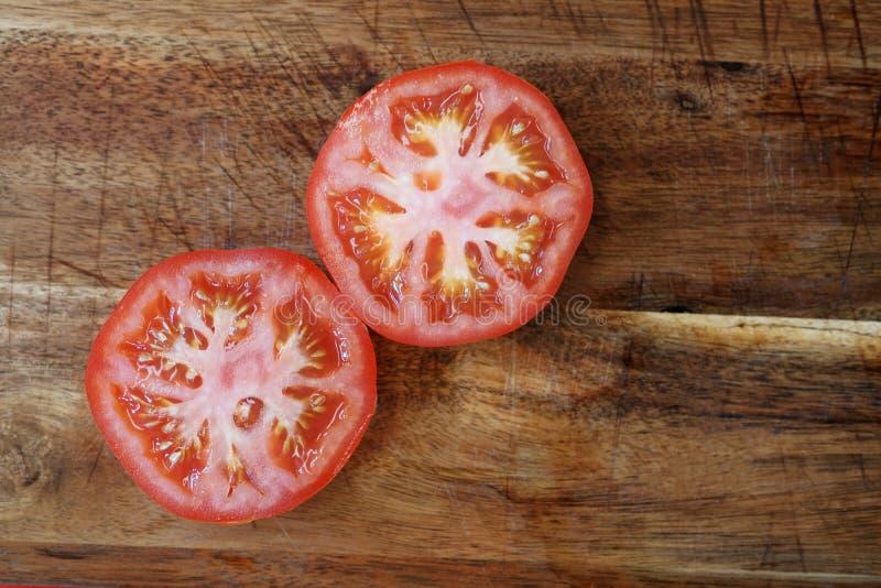 Tomatskivor på träbräde royaltyfri foto