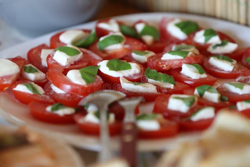 Tomatsnitt i halva med spenatdeg royaltyfri bild