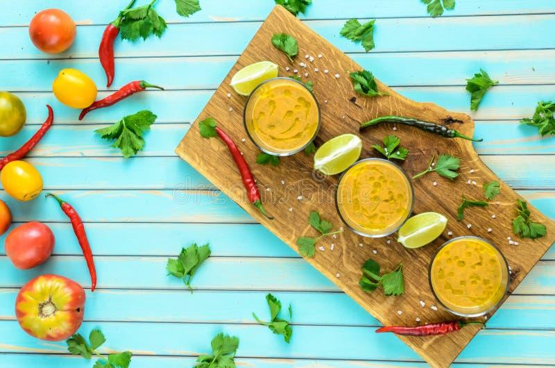 Tomatsoppagazpacho och ingredienser över turkosträbakgrund arkivbilder