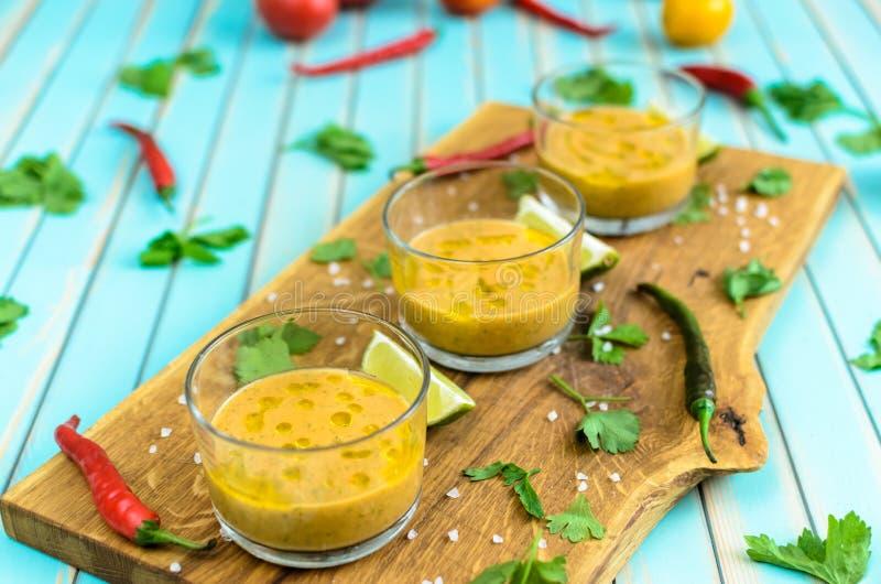 Tomatsoppagazpacho och ingredienser över turkosträbakgrund royaltyfri foto