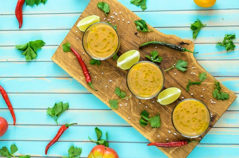 Tomatsoppagazpacho och ingredienser över turkosträbakgrund arkivfoto