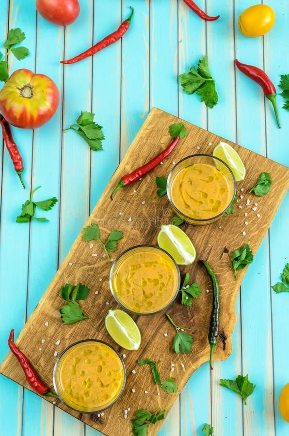 Tomatsoppagazpacho och ingredienser över turkosträbakgrund royaltyfri bild