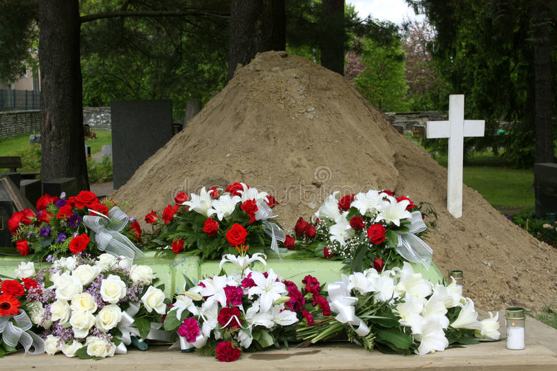 Tomba con i fiori e la traversa fotografie stock