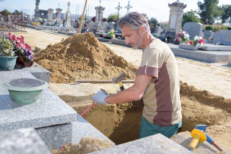 Tomba di scavatura dell'uomo caucasico al cimitero fotografia stock libera da diritti
