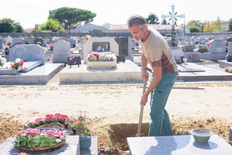 Tomba di scavatura dell'uomo in cimitero fotografia stock libera da diritti