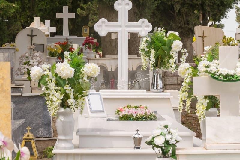 Tombe avec des fleurs à un cimetière photographie stock libre de droits