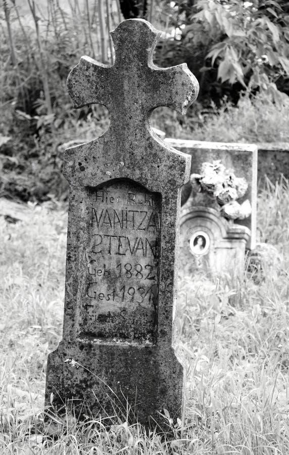 Tombestone torcido resistido viejo de Christian Catholic en el cementerio en blanco y negro foto de archivo