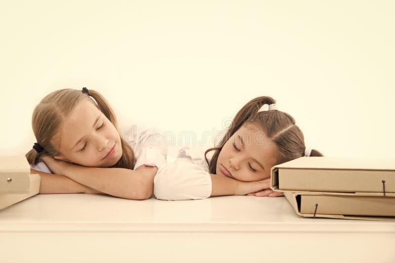 Tombez endormi sur la le?on Les filles tombent endormi tandis que fond de blanc de projet d'?cole de travail ?coli?res fatigu?es  photo stock