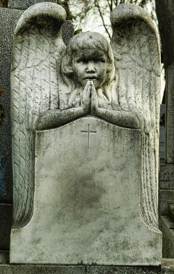Tombstone angel praying. Old blank tombstone with praying angel statue royalty free stock photography