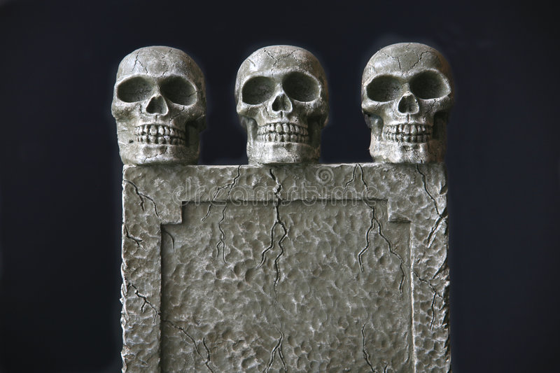 Tombstone Trio. A trio of skulls sit atop a blank tombstone with space for your copy. Great Halloween image and also a useful conceptual image for smoking stock photography