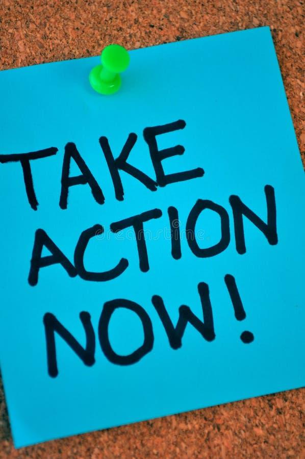 Tome a ação anotam agora no quadro de anúncios fotografia de stock