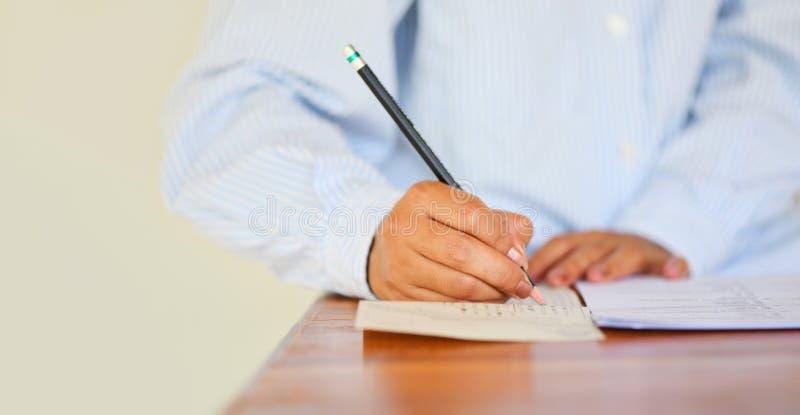 Tome ao exame a escrita final do lápis da terra arrendada da estudante universitário da High School na folha de resposta de papel foto de stock
