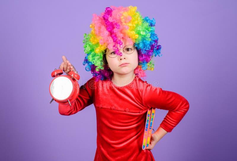 Tome el cuidado de su tiempo Ni?o juguet?n lindo de la muchacha llevar la peluca rizada del arco iris La vida es diversi?n Ni?ez  foto de archivo libre de regalías