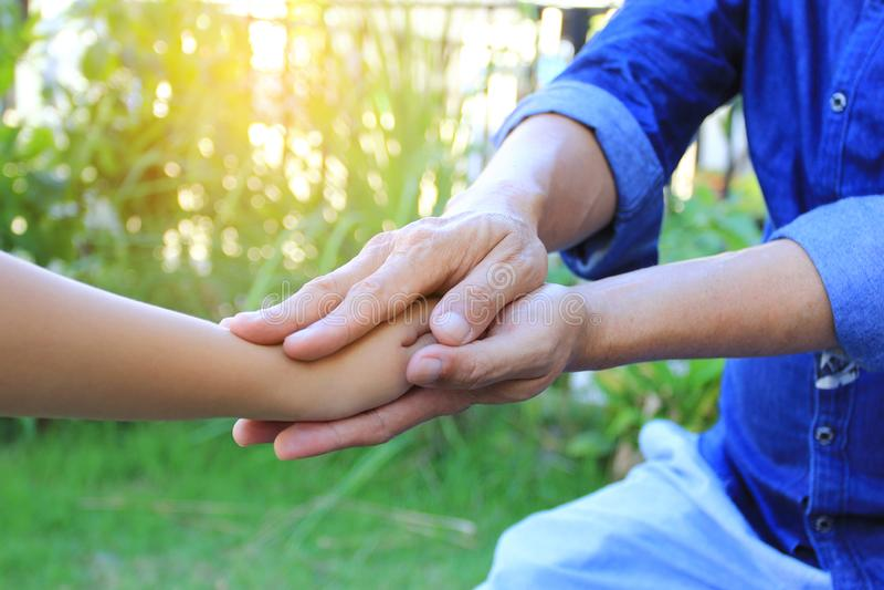 Tome el cuidado, hombre mayor que lleva a cabo las manos de la muchacha del pequeño niño en fondo verde natural fotos de archivo