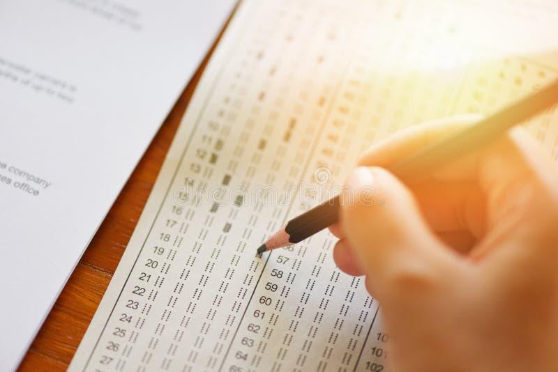 Tome a examen la escritura final del lápiz de la tenencia del estudiante de la mano de la escuela secundaria en la hoja de respue imágenes de archivo libres de regalías
