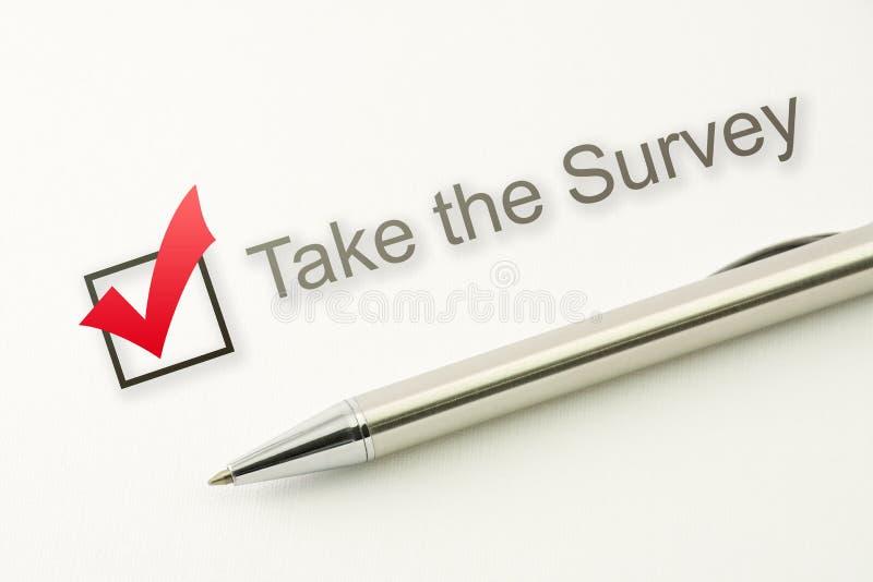 Tome la caja de control de la encuesta con una pluma en el fondo de papel fotografía de archivo