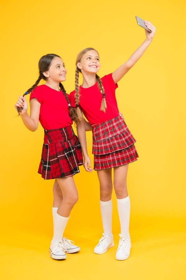 Tome la foto perfecta Las muchachas apenas quieren divertirse Las colegialas utilizan el smartphone del teléfono móvil que toma l fotos de archivo libres de regalías