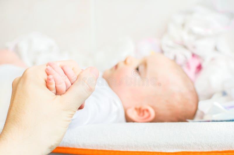 Tome la mano del bebé que miente en la tabla cambiante fotografía de archivo libre de regalías
