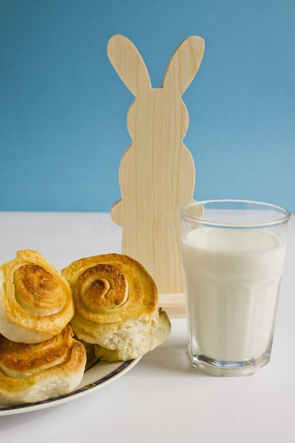 Tome o café da manhã com bolos de canela e vidro do leite em um fundo azul com coelhinho da Páscoa da decoração imagem de stock royalty free