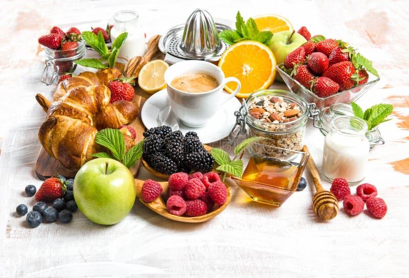 Tome o café da manhã com café, croissant, muesli, bagas, frutos fotografia de stock royalty free