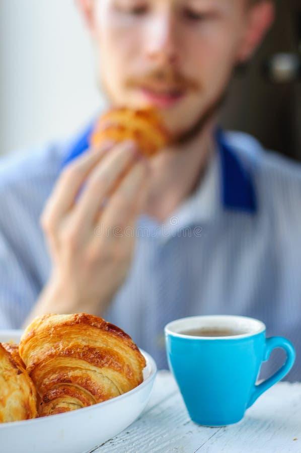 Tome o café da manhã com café e croissant com o homem novo no fundo foto de stock