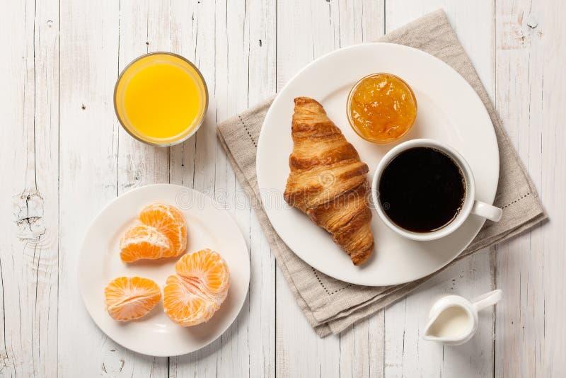 Tome o café da manhã com croissant, doce do café, suco de laranja e mandarino foto de stock