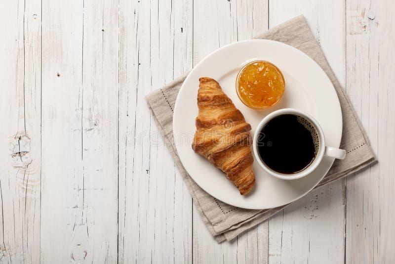 Tome o café da manhã com croissant, café e doce alaranjado imagem de stock royalty free